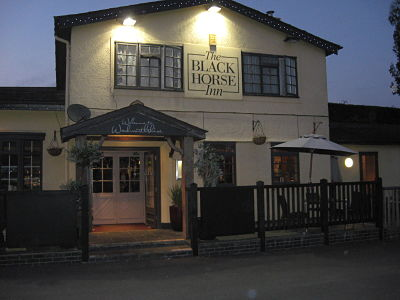 Picture of the Black Horse Inn, evening with lights on.